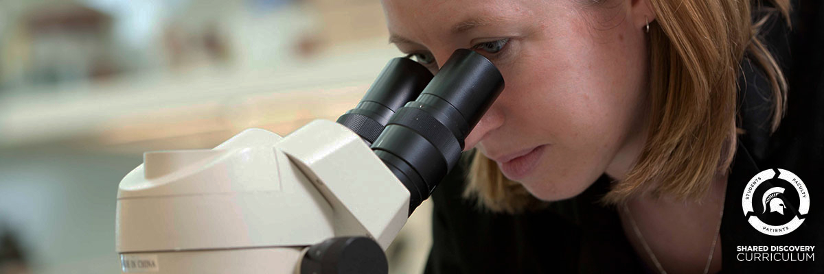 image of woman looking in microscope